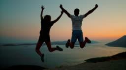 MS Super slow motion couple jumping for joy at scenic ocean overlook at dusk,Peljesac,Croatia