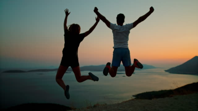 ms super slow motion couple jumping for joy at scenic ocean overlook at dusk,peljesac,croatia - exhilaration stock videos & royalty-free footage