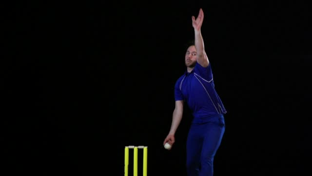 super slow motion -   cricket bowler in blue bowls the cricket ball - cricket bowler stock videos and b-roll footage