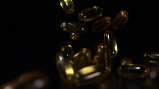 vídeos de stock e filmes b-roll de super slow motion: fish oil drop on black background - vitamina a