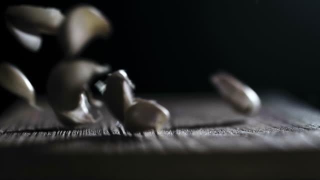 Super slow motion : Garlic on rustic wood