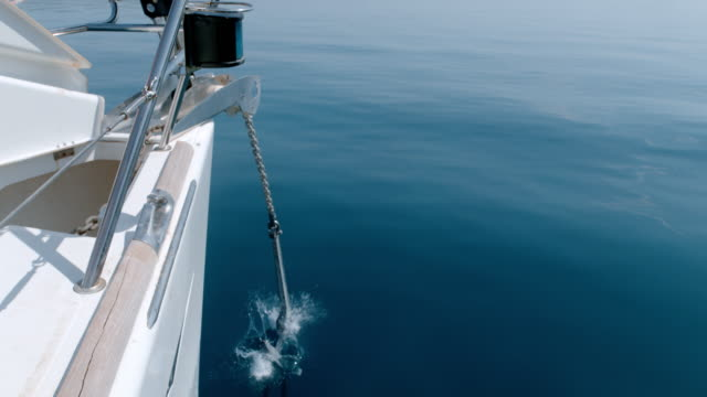 vídeos de stock e filmes b-roll de ms super slow motion hand dropping anchor off sailboat - ancora