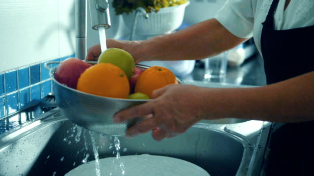 super slow motion : hands washing fruits close up. - hygiene stock videos & royalty-free footage