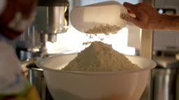Super slow motion macro of flour falling on the bakery table (extra close up)