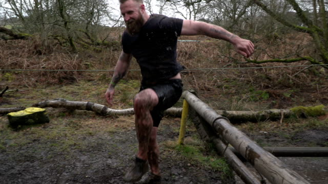 Super Slow Motion: Male Jumping from water in Mud Run Assault Course / Obstacle Course