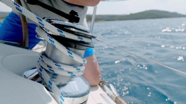 cu super slow motion man adjusting rigging on sailboat - yachting stock videos & royalty-free footage