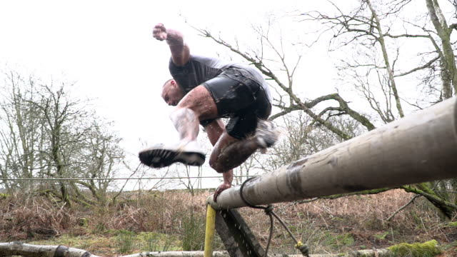 Super Slow Motion: Man Jumping from water in Mud Run Assault Course / Obstacle Course