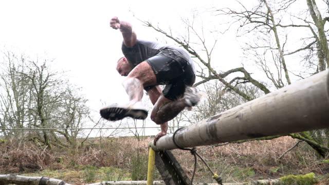 vídeos de stock, filmes e b-roll de super câmera lenta: homem saltos de água na lama executar assault course / curso de obstáculo - lama