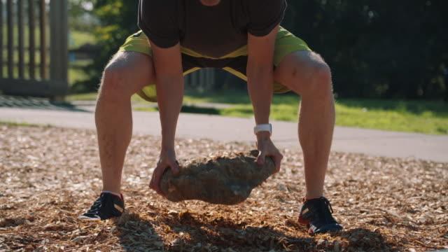 hd super slow motion middle aged athlete lifting a stone and throwing it. - stenstorlek bildbanksvideor och videomaterial från bakom kulisserna