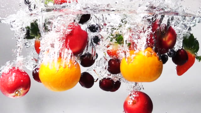 vídeos de stock e filmes b-roll de super slow motion: mix fruit drop into fresh water on white background - juicy