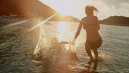 MS Super slow motion mother and daughter jumping into sunny,idyllic ocean at sunset,Peljesac,Croatia