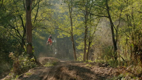 ms super slow motion motocross rider jumping above sunny dirt course in woods - 1 minute or greater stock videos & royalty-free footage