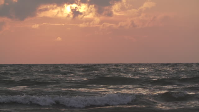 Super slow motion ocean waves at sunset