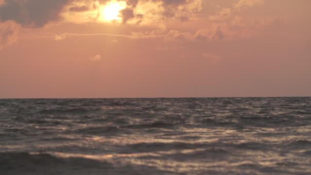 Super slow motion ocean waves at sunset