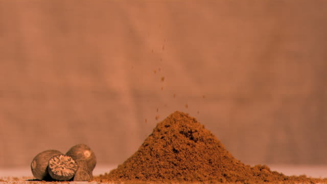 super slow motion of nutmeg powder falling - brown background stock videos & royalty-free footage
