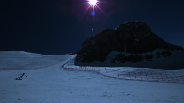 Super slow motion of skier skiing down slope by night.