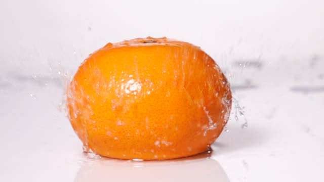 super slow motion: orange falling on table with water splashing - ascorbic acid stock videos & royalty-free footage