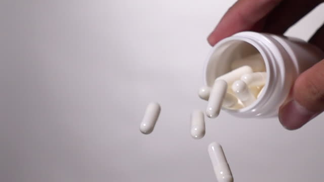 super slow motion: pouring capsule from bottle on white background - aspirin stock videos & royalty-free footage