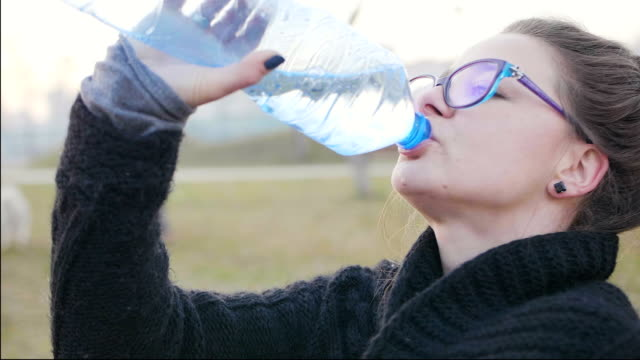 Super slow motion shot of a girl sitting in the park and drinking mineral water from a plastic bottle