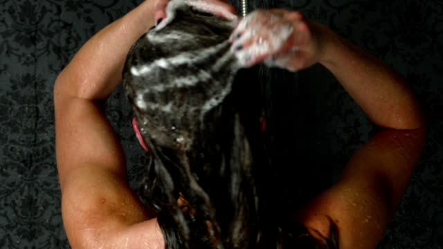 Super slow motion shot of a girl taking a shower or bath and washing her hair