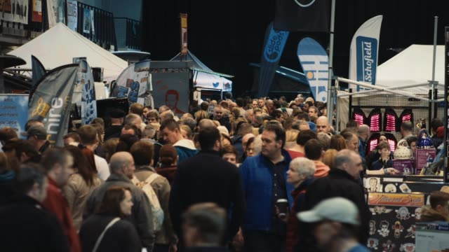 super slow motion shot of a large crowd of people walking at a live event in a convention center. filmed at camper mart / tattoo freeze 2016, uk. no... - tattoo stock videos & royalty-free footage
