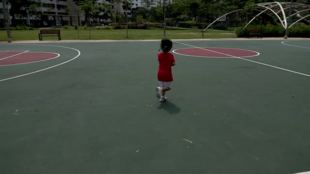 super slow motion shot of a little girl running in the outdoor basketball court - one girl only stock videos & royalty-free footage