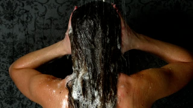 Super slow motion shot of a young adult female taking a shower or bath and washing her hair