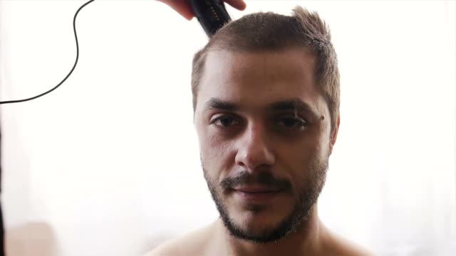 super slow motion shot of a young man looking at camera and getting his hair cut with hair cutting machine - cutting hair stock videos and b-roll footage