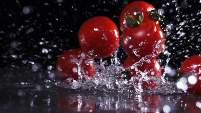 stockvideo's en b-roll-footage met super slow motion: tomaat die op de vloer valt met opspattend water - rijp voedselbereiding