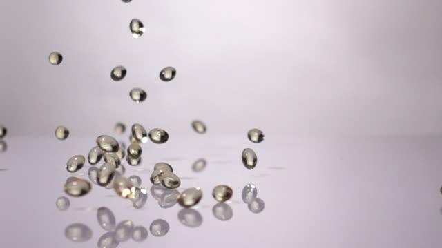 vídeos de stock e filmes b-roll de super slow motion: vitamin drop on white background - vitamina a