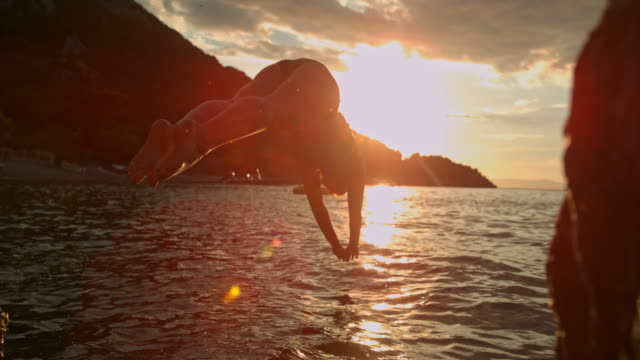 ms super slow motion woman diving into tranquil ocean at sunset,peljesac,croatia - perfection stock videos & royalty-free footage