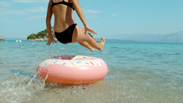 ms super slow motion woman jumping onto inflatable ring in sunny summer ocean,peljesac,croatia - inflatable stock videos & royalty-free footage