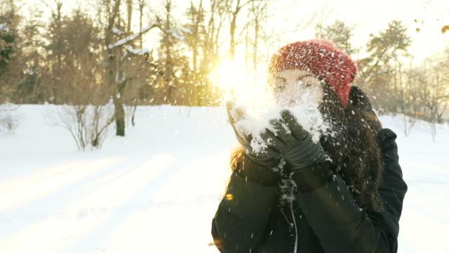 stockvideo's en b-roll-footage met super slowmotion: jonge vrouw waait sneeuw vlokken in een zonnige winterdag. - sunny