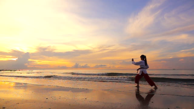 hd super slow motion: young women practising martial arts outdoors on the beach at sunset time - curiosity stock videos & royalty-free footage