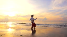 HD Super Slow motion: Young women Practising Martial Arts Outdoors On the beach at Sunset time