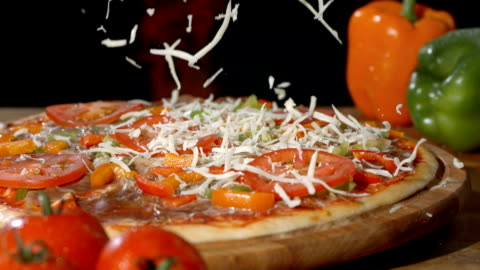 hd super slow-mo: adding a sprinkle of cheese on pizza - pizza stock videos & royalty-free footage