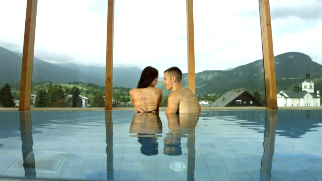 hd super slow-mo: affectionate couple in the pool - swimwear stock videos and b-roll footage