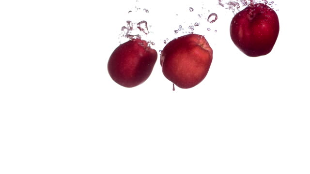 hd super slow-mo: apples splashing into water - apple fruit stock videos & royalty-free footage