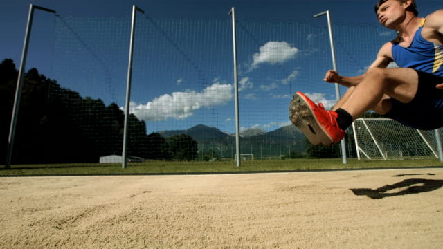 hd super slow-mo: athlete landing in sandpit - long jump stock videos & royalty-free footage