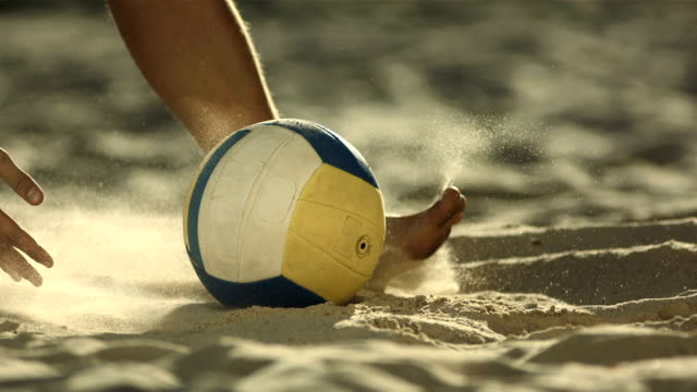 stockvideo's en b-roll-footage met hd super slow-mo: beach volleyball player picking up a ball - bal