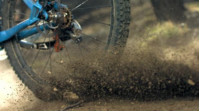 super slow-mo: biker kicking sand while speeding along trail - gara off road video stock e b–roll