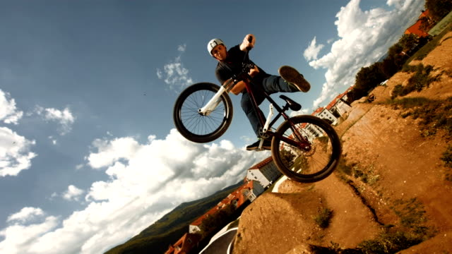 hd super slow-mo: bmx dirt rider performing unturndown trick - bmx cycling stock videos and b-roll footage