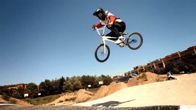 hd super slow-mo: bmx riders jumping over double jump - bmx cycling stock videos and b-roll footage