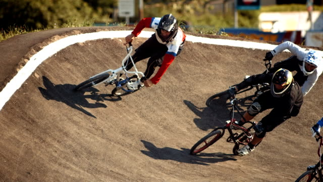 hd super slow-mo: bmx riders racing along berm - freestyle bmx stock videos and b-roll footage