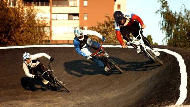 hd super slow-mo: bmx riders racing in berm - bmx cycling stock videos and b-roll footage