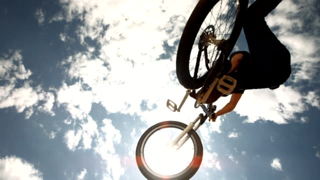 hd super slow-mo: bmx stunt rider performing tail whip - bmx cycling stock videos and b-roll footage