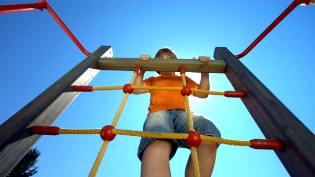 stockvideo's en b-roll-footage met hd super slow-mo: boy climbing on a jungle gym - speeltuin