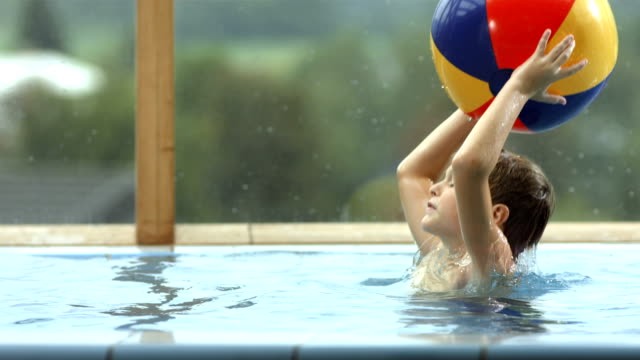 hd super slow-mo: boy throwing a ball in the pool - inflatable stock videos & royalty-free footage