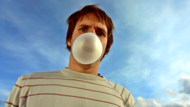 hd super slow-mo: bubble popping over face - bubble gum stock videos & royalty-free footage