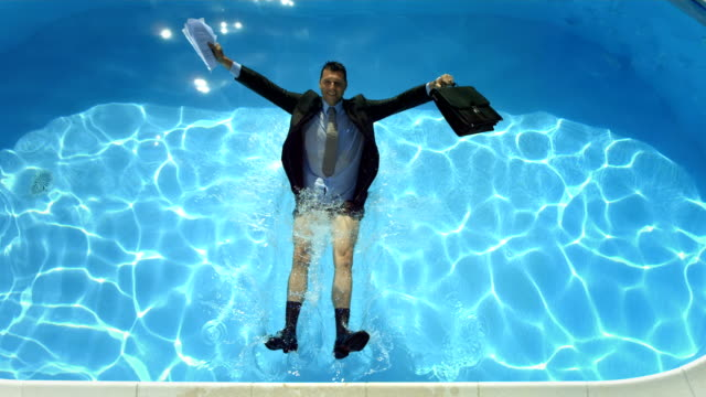 hd super slow-mo: businessman falling into swimming pool - tripping falling stock videos and b-roll footage